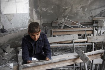 Syrian boy reads a torn paper inside his destroyed school classroom © AP / Reporters